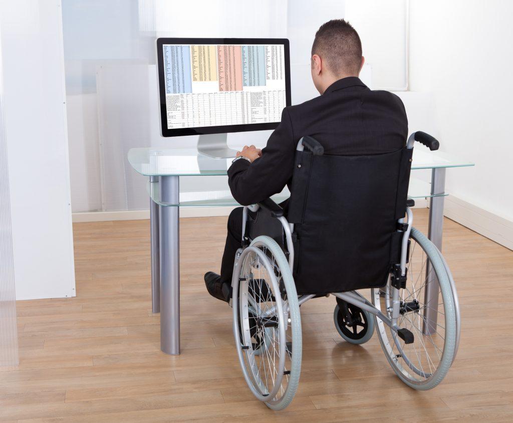 Businessman On Wheelchair Using Computer